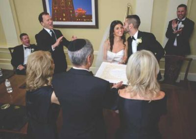 Amanda and Mike sign the ketubah with parents and Rabbi Micah Greenstein.