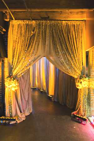 Guests entered the hallway of golden drapes (thanks to Holliday Flowers & Events, Classic Party Rentals, Cloth Connection Linens