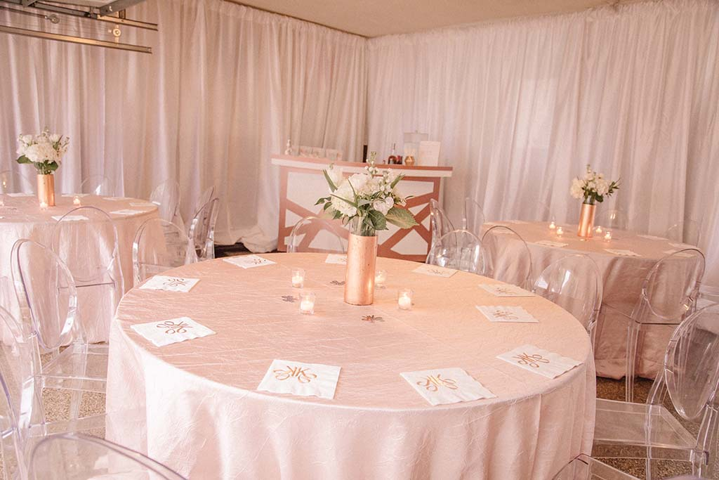 Outdoor plans changed when rain was inevitable, and Holliday Flowers transformed the garage into an intimate setting by draping the walls, and bringing in a cocktail bar, beautiful flowers, linens and chairs.